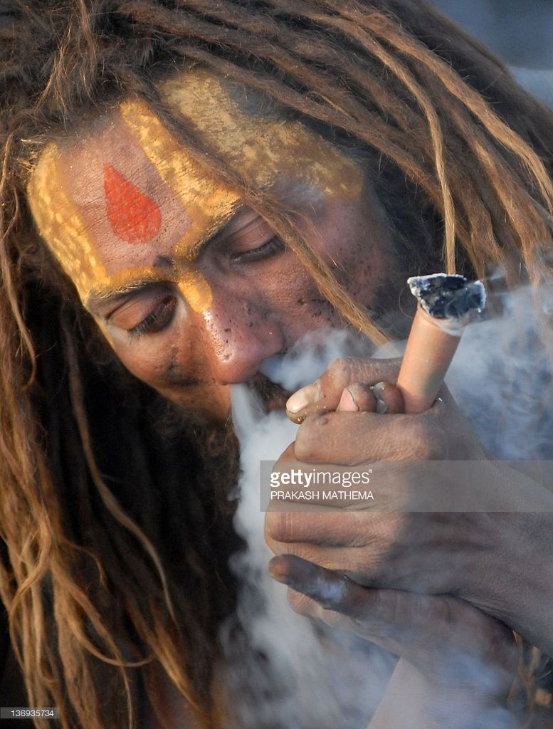 A Sadhu smokes ganja in a chillum as a holy offering from Lord Shiva,...