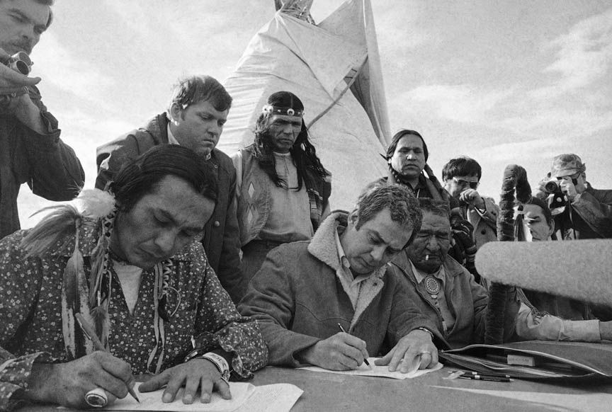 Russell Means, left, and assistant U.S. attorney general Kent Frizzell sign the Wounded Knee settlement on April 5, 1973 in South Dakota. Looking on left is Frizzell's assistant Richard Helstern and AIM leader Dennis Banks.