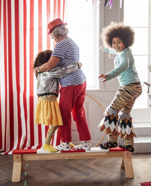 Kuvassa kaksi lasta ja heidän isoäitinsä tasapainottelevat penkillä.