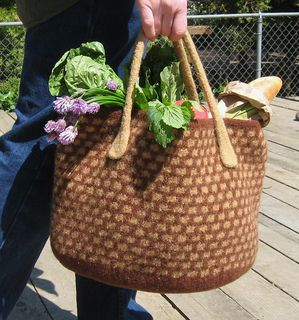 "Here's the perfect tote for a trip to the farmer's market. This felted bag has a 2 color slip stitch pattern that mimics basketry. The solid colored bottom is oval shaped and gently rounds into the straight sides. The bag is knit of bulky weight yarn and then felted to create a very dense sturdy fabric. The pattern includes directions for felted I-cord handles. Finishing at approximately 15"" across and 10"" high, it's big enough to accommodate all of your purchases. Basic instructions for ..."