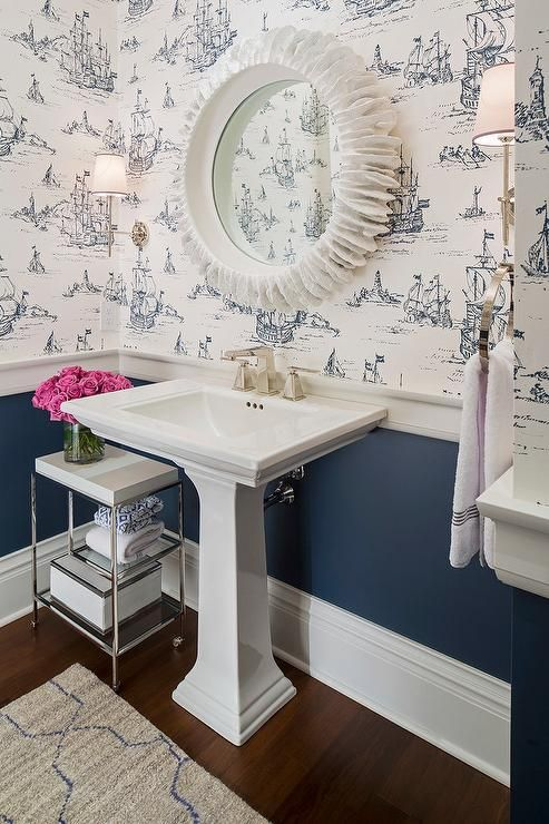 White and navy powder room features top half of walls clad