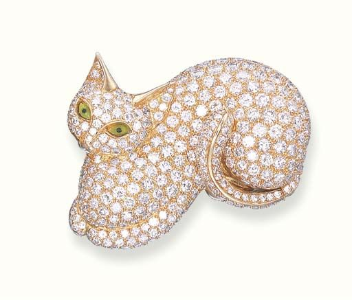 A DIAMOND-SET CAT BROOCH. Designed as a pavé-set diamond cat with green and black enamel eyes, mounted in 18k gold, with French assay marks for gold