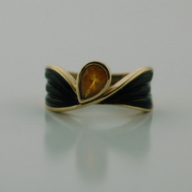 Lady's 14K Yellow gold citrine and onyx ring. The free shaped ring set with one pear shaped citrine and two carved onyx pieces. Gold weight 2.75 DWTs.