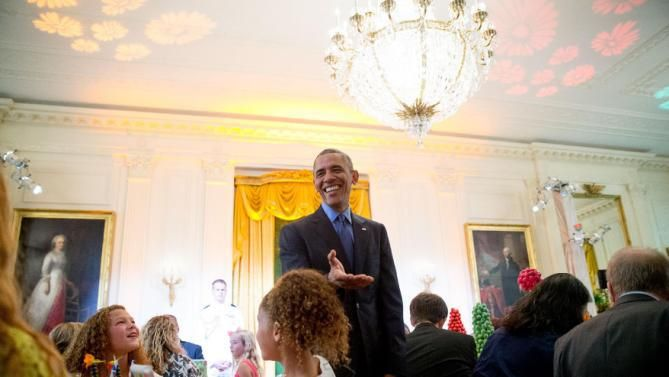 President Barack Obama greets Sophia and Isabella Strahan, the daughters of retired football player Michael Strahan, as he makes an unannounced appearance as first lady Michelle Obama hosts the 2015 winners of the Healthy Lunchtime Challenge for the Kids' State Dinner in the East Room at the White House, Friday, July 10, 2015, in Washington. (AP Photo/Andrew Harnik)