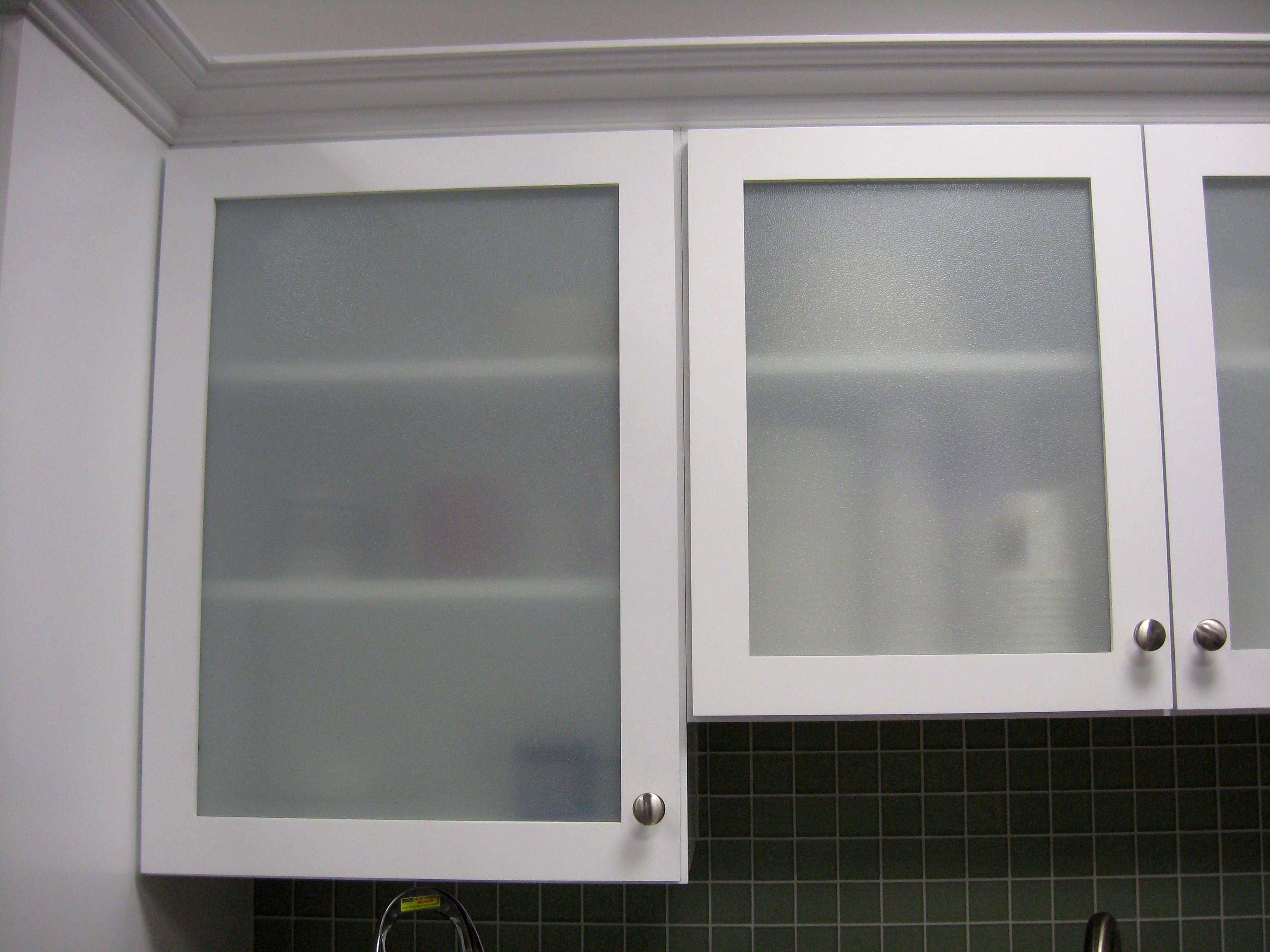 The glass doors on these gray kitchen cabinets lend a modern feel