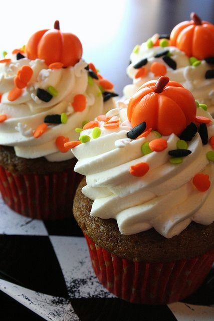 Pumpkin spice cupcakes topped with whipped cream cheese frosting, Halloween sprinkles, and a marshmallow fondant pumpkin!