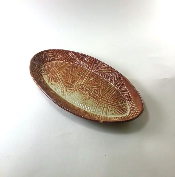 This oval Plate could be a side plate or a condiment dish.  I have one on my dresser that holds my watch, rings and  bracelets, when I am in the shower.I made this with a slab of clay.  After the clay is rolled out, I smooth the slab and then texture it with an Intaglio Stamp Mat from another Etsy Seller BHClaysmith ; this one is called Dot Leaf.  I usually texture the entire slab with the mat.  I draped this slab over an oval form and rolled the back of it to form fit the plate.  After it firms