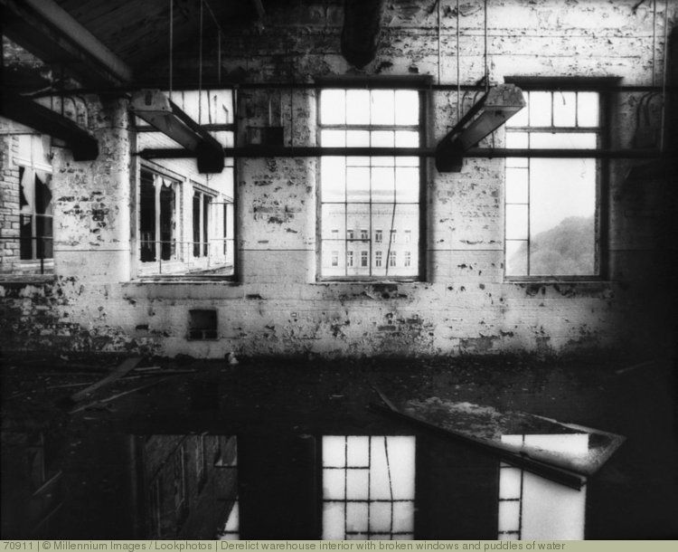Derelict warehouse interior with broken windows and puddles of water