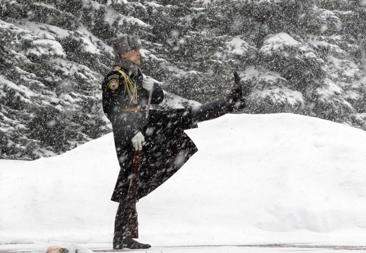 Russian Soldier Guarding Tomb of the Unknown Soldier by the Kremlin wall during snowfall in