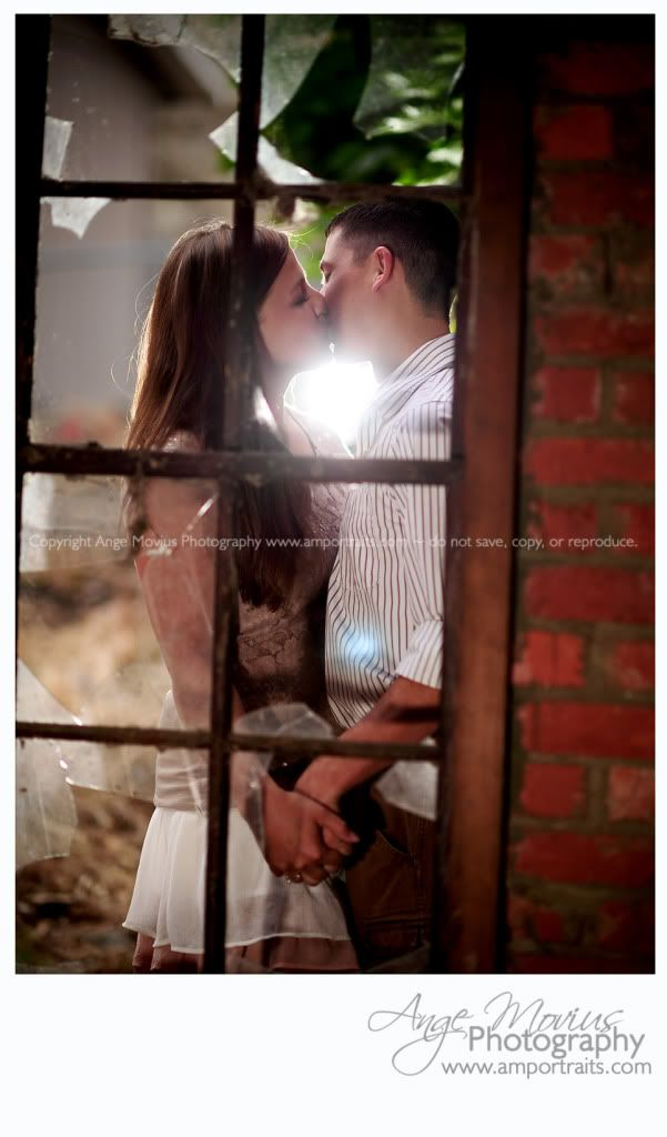 Looking through the window a an Engagement session couple portrait brick wall window light www.amportraits.com