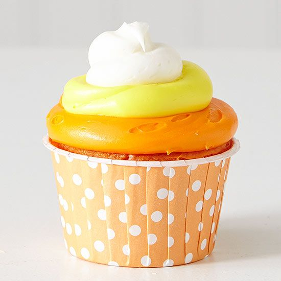 Enjoy the classic Halloween candy as a cute cupcake! For an extra adorable touch, top with a candy corn. To make these Halloween cupcakes, use these cupcake decorating steps: 1. Tint a portion of white frosting with orange food coloring. Tint a second portion with yellow food coloring. Keep another portion plain white. 2. Place each frosting color in its own pastry bag with a large round tip. Pipe frosting on cupcakes to resemble candy corn.  /