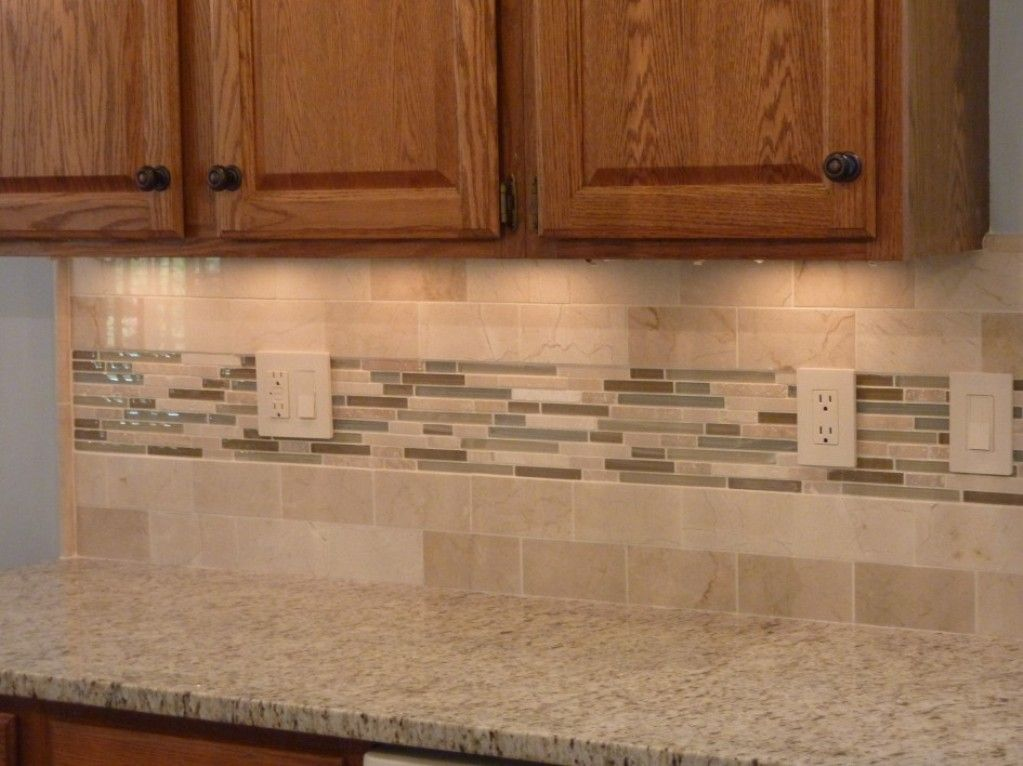 Subway tile backsplash laid in offset pattern with glass tile accent.