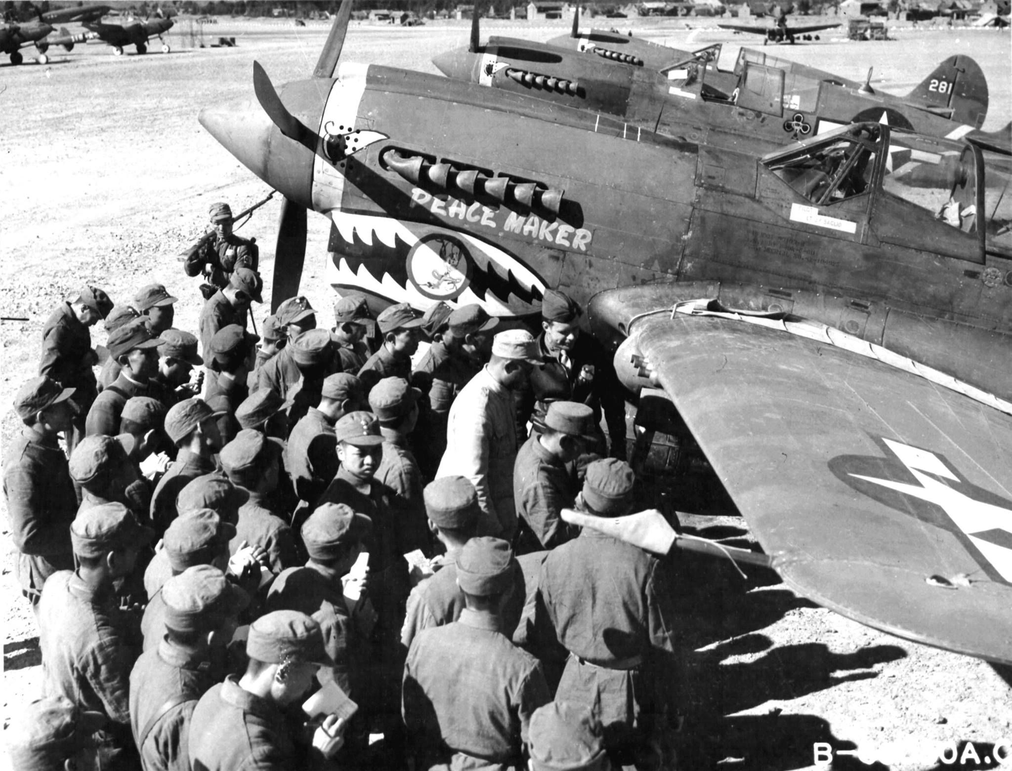 """Chinese soldiers, who are training to become aircraft spotters, looking over the features of the P-40 """"Peace Maker"""", at a 14th Air Force Base in China. (NA)."""