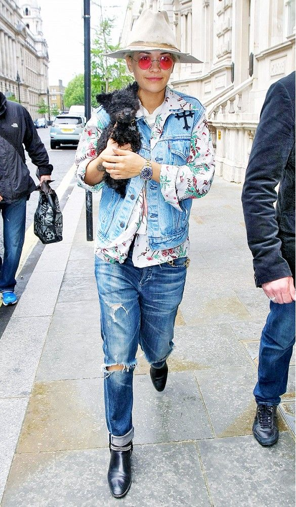 Rita Ora wears a printed shirt, denim vest, oversized jeans, motorcycle boots, round sunglasses, and a fedora