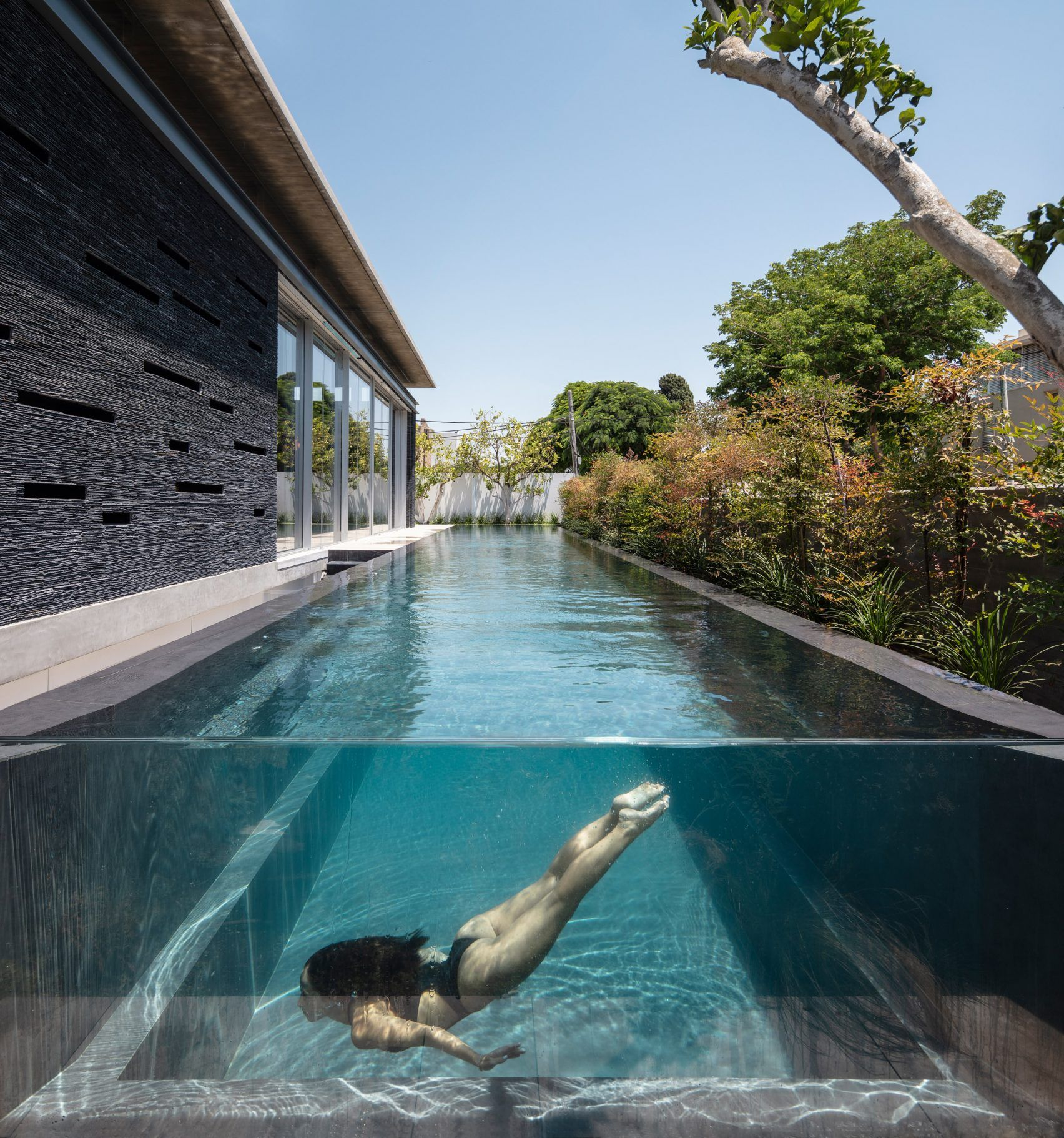 Linear Swimming Pool Runs Parallel To Slate Clad Pavilion House By