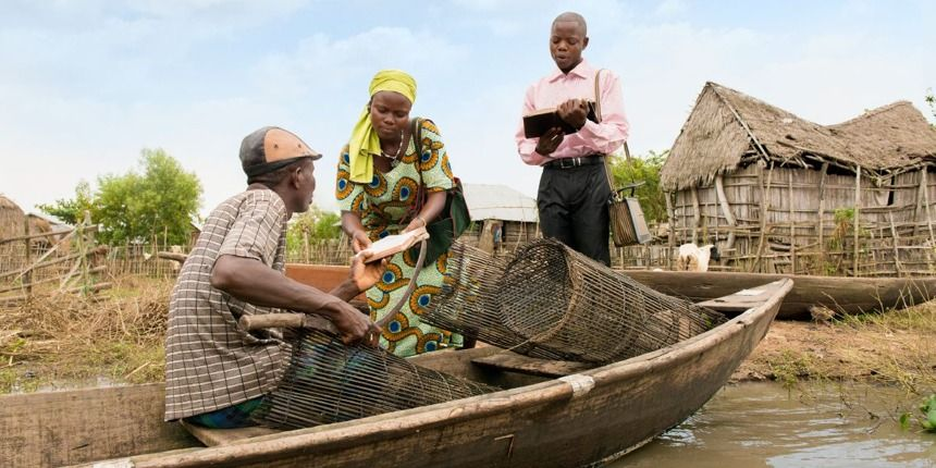 Jehovah's Witnesses in Benin preach to a man in a canoe
