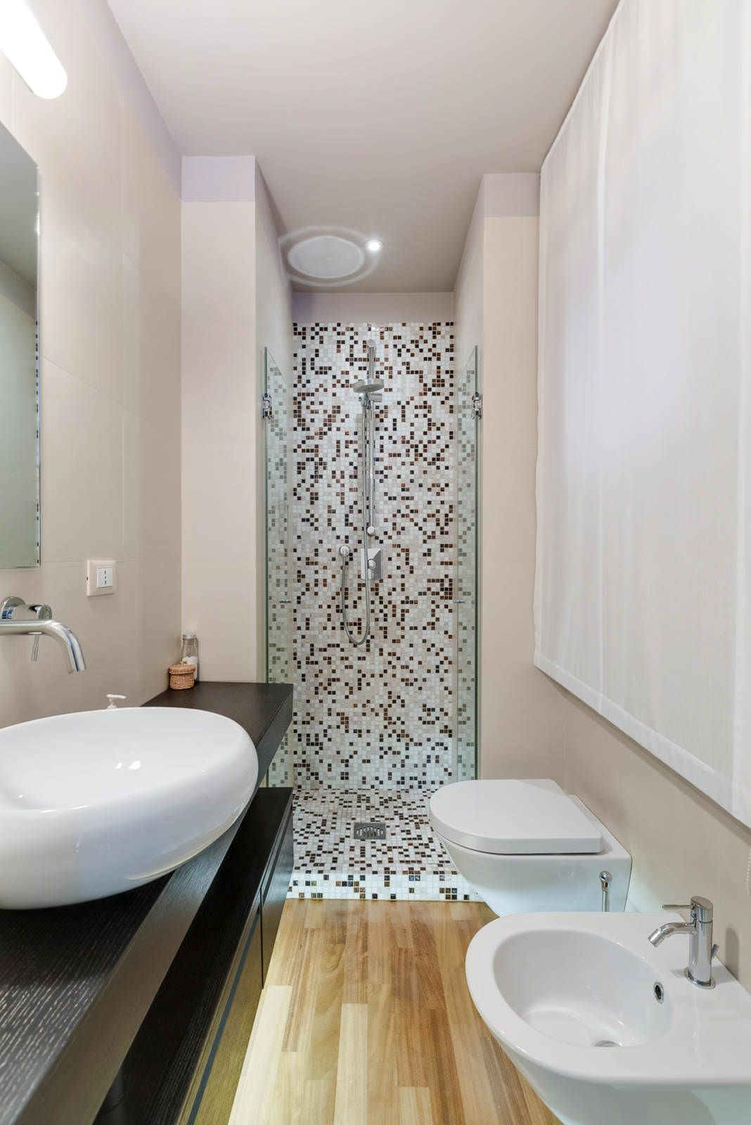 Design bagno piccolo, stretto e lungo, con la doccia posizionata in fondo  alla stanza, rivestita in mosaico , moderna ed elegante