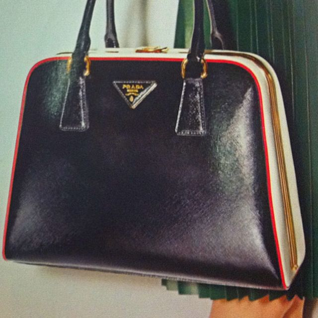 5a7ee949ae91 Bowling-style Prada Pyramid Frame handbag. Love the green dress paired with  this retro black-white-red bag