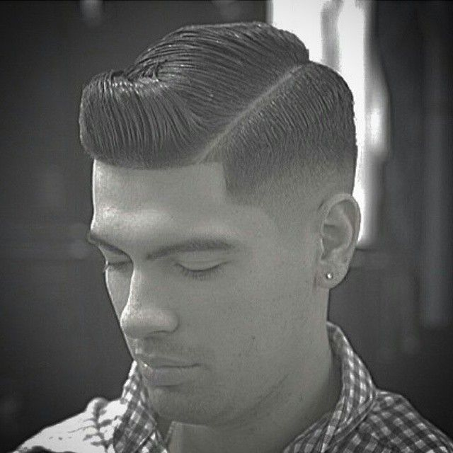 A crisp razor part with an executive contour style. Well blended on the sides & dressed with ...
