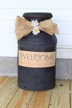 Transformed an old rusty milk can from the garage into a plant stand for the front porch. Just removed all the rust and dirt and painted black. Added a 97 cent vinyl wall quote from Walmart. Spray with clear coat and you are done. So easy