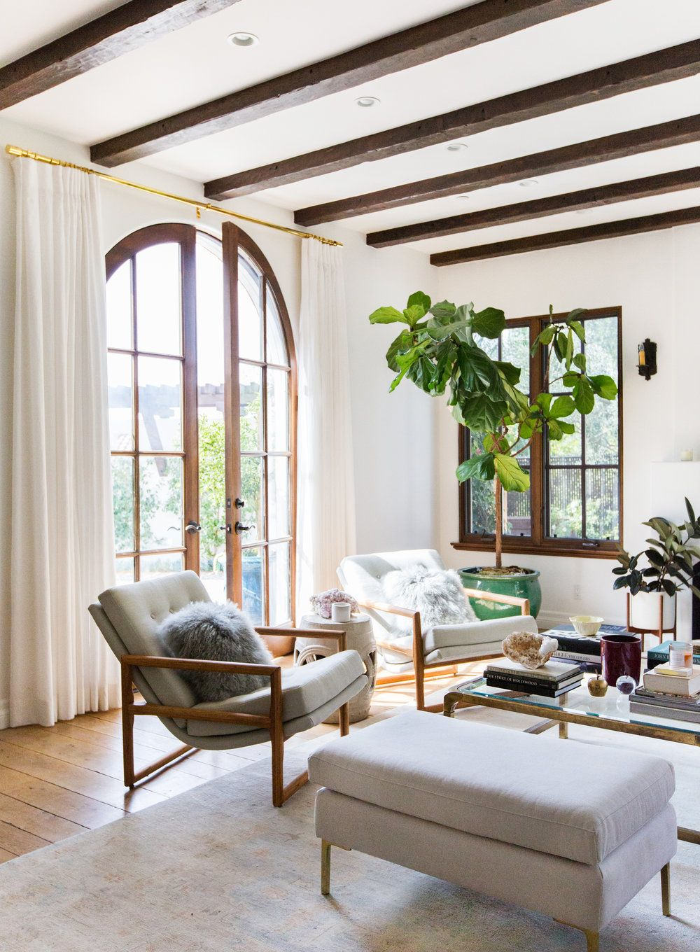 White open living area with dark exposed beams and tall pane doors ...