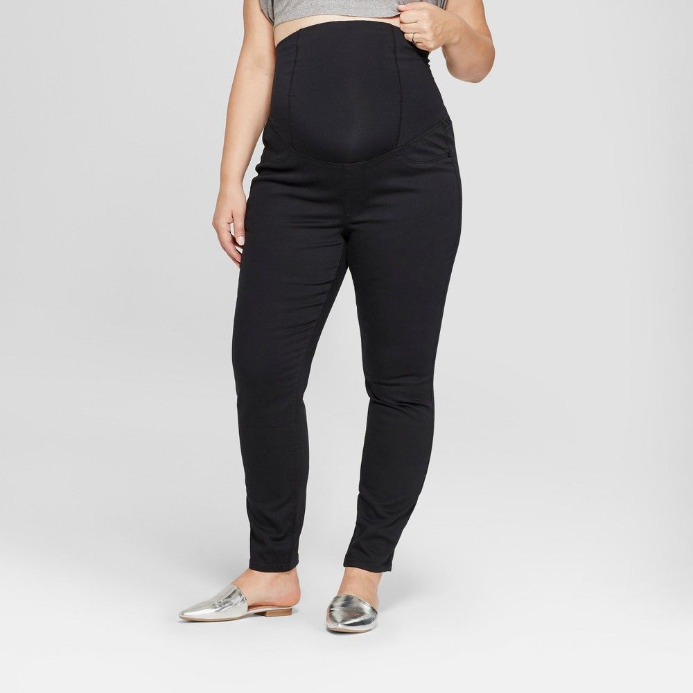 02ce2ef4cd0d5 A classic maternity skinny jean in black denim. Power stretch denim shapes  and sculpts while adjusting to your changing body. The Crossover Panel  provides ...