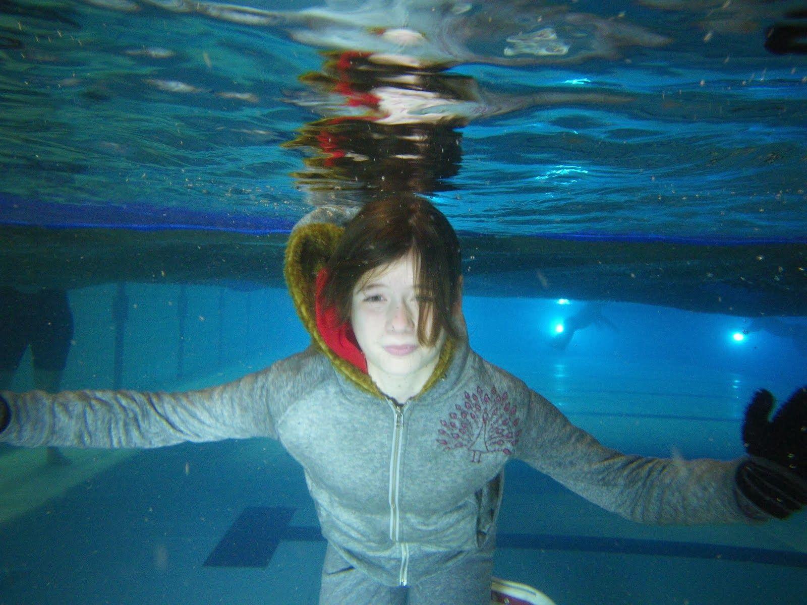 Girl underwater with winter clothes girls underwater at school