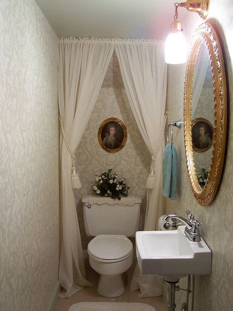 decorating your under stairs space with elegant bathroom design with large rounded mirror also white sink and toilet with white curtains cover