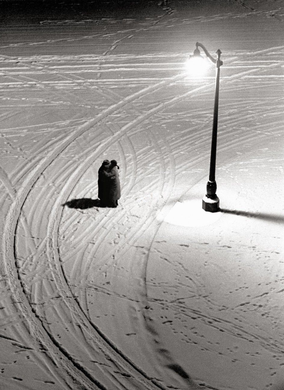 Fred Stein Archive - Embrace. High angle, nighttime view of a couple as they stand under a street light and embrace on a snowy street corner, Paris, France, 1934. °