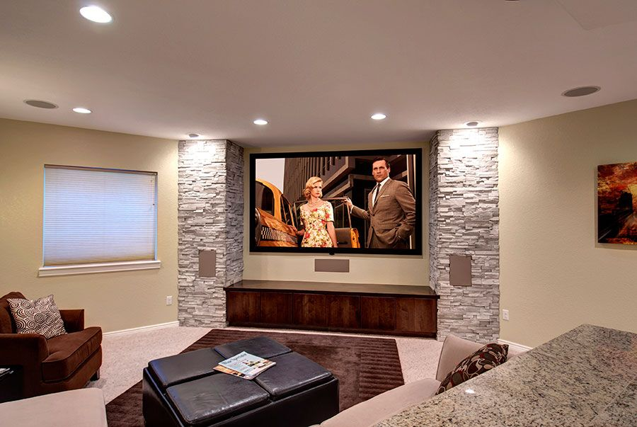 The big screen tv is anchored by stone walls on either side and built ins conceal all the - Home theater screen wall design ...