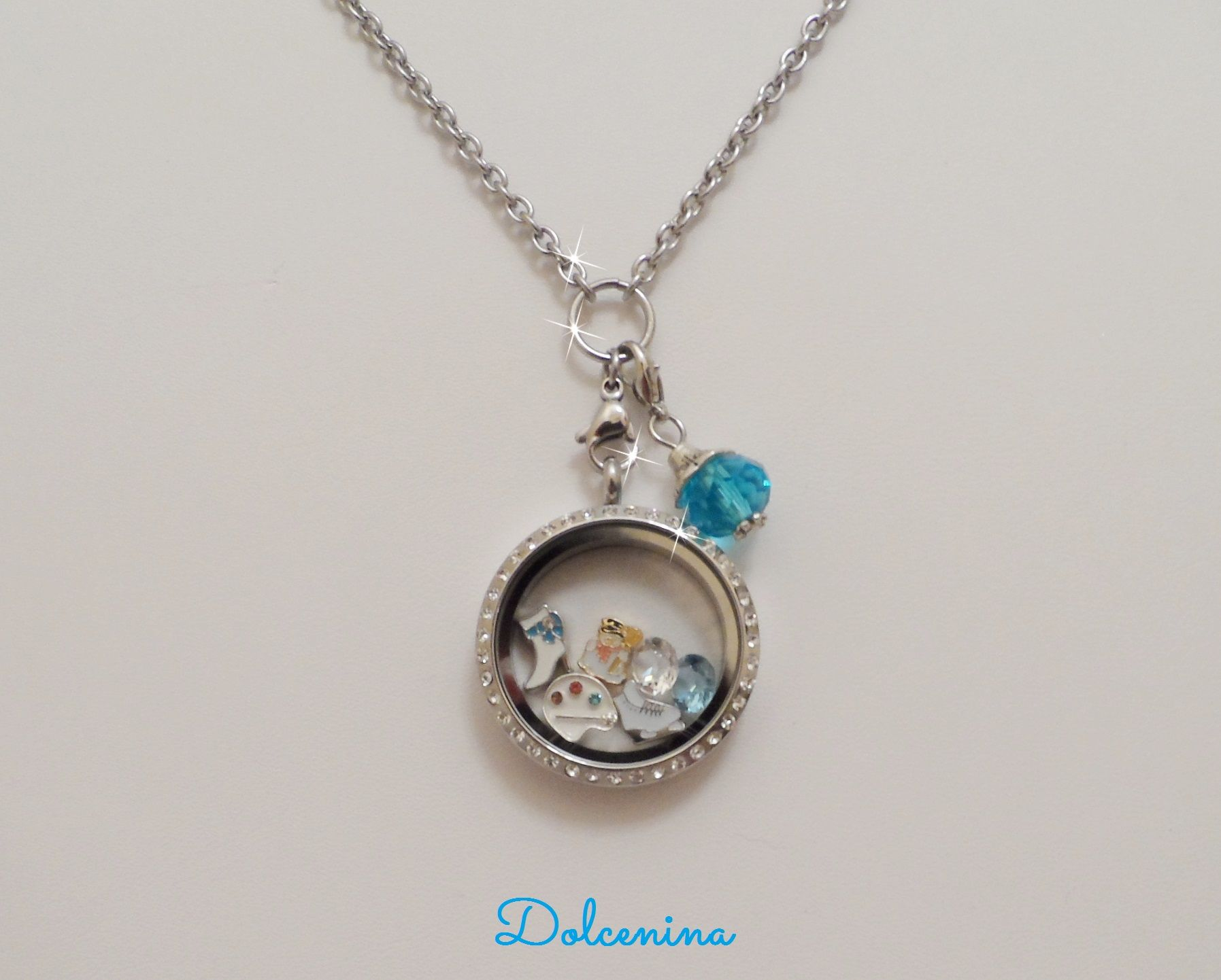 Fashion forward style, this beautiful and stylish locket is a cute locket theme for the winter, has boot charm, an ice skate charm, a  snowman, a clear diamond crystal and a sky blue crystal locked up in a Large Clear Diamond Crystal Locket with a light blue crystal dangle.