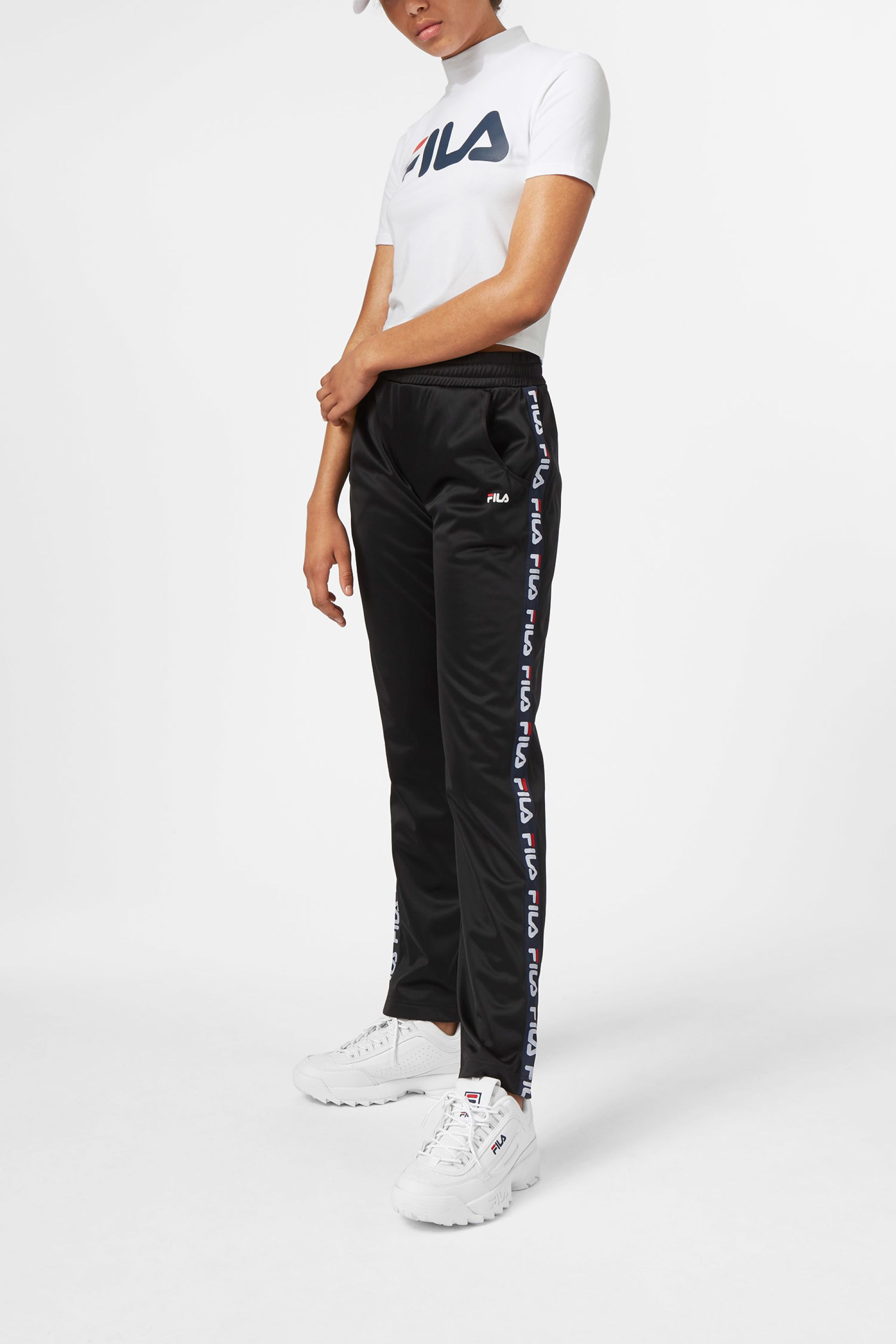 10d789773427a The Strap Track Pants by Fila are a pair of unisex tracksuit pants adorned  with tapes with the brands iconic logo. Made of a soft and sleek material,  they