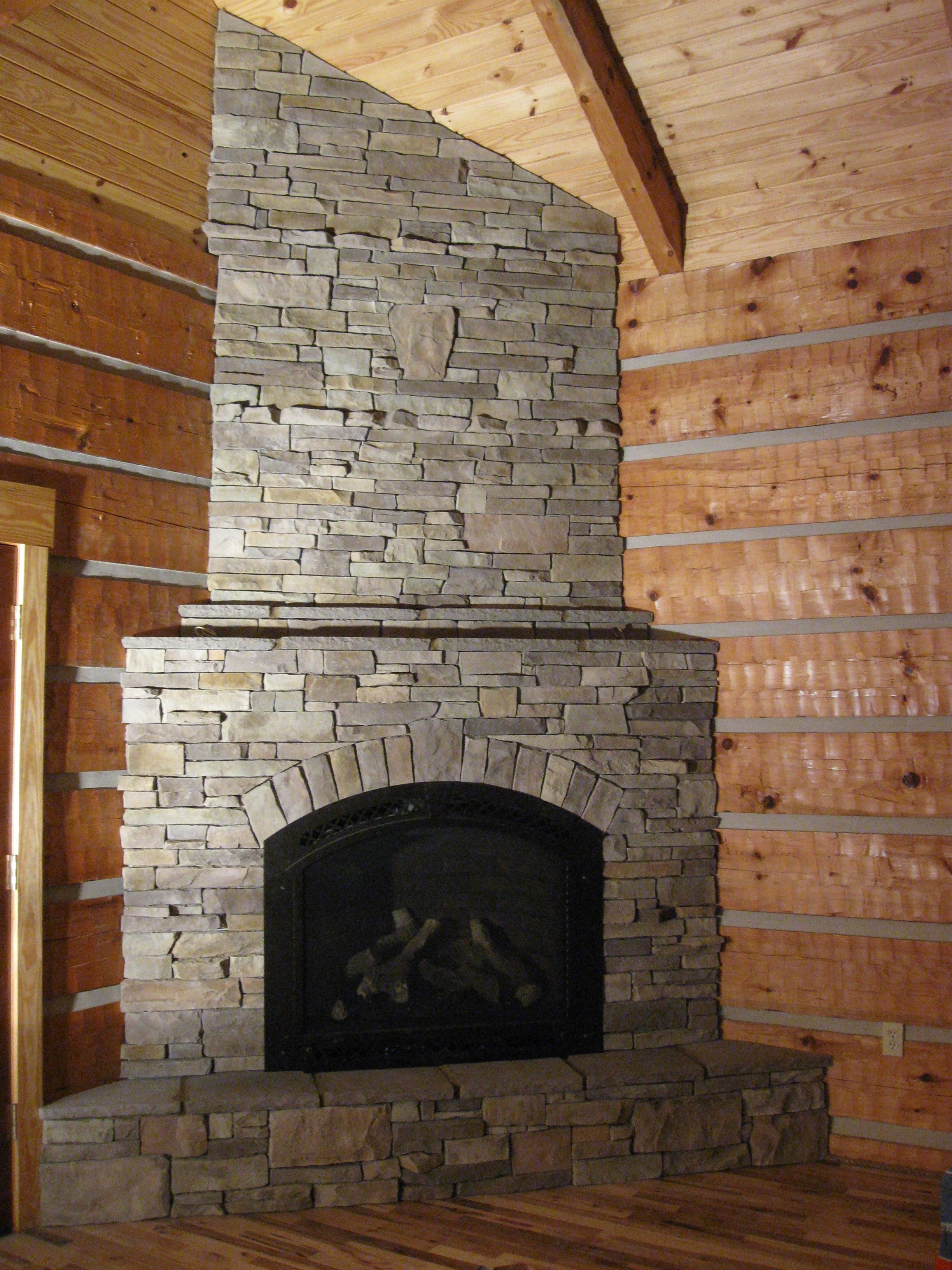 Corner fireplace in stack stone old barn board ideas for Corner fireplace plans