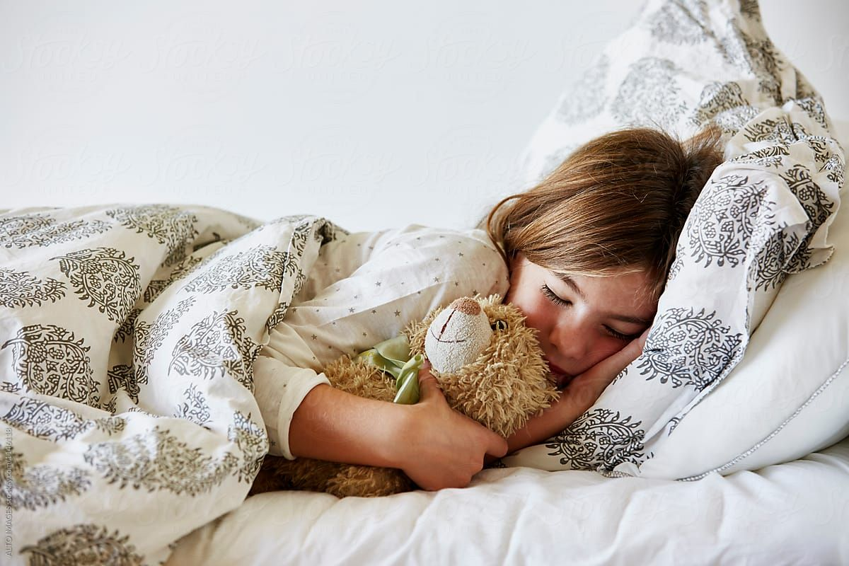 Girl sleeping with her soft toy in bed by alto images for