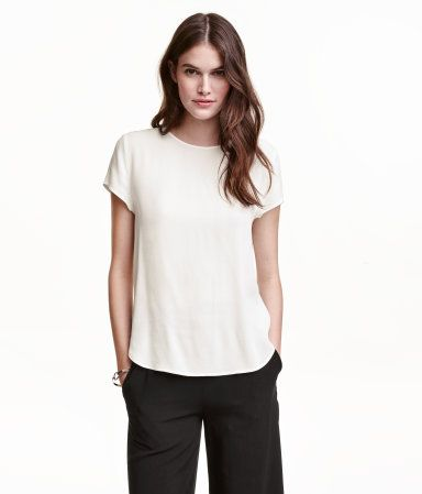White. Short-sleeved blouse in crêped, woven viscose fabric. Opening at back of neck with button. Rounded hem, slightly longer at back.