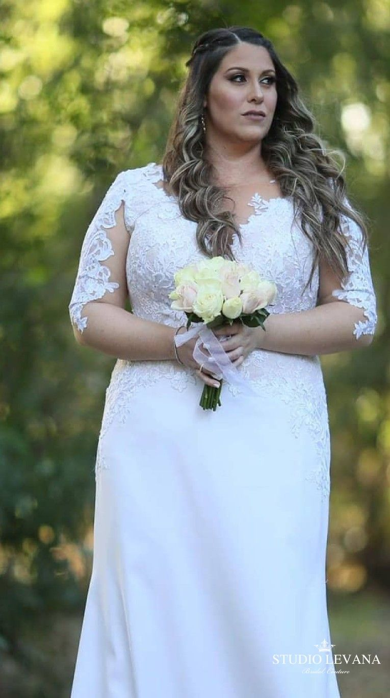 Real plus size bride in a fitted corset wedding gown with long