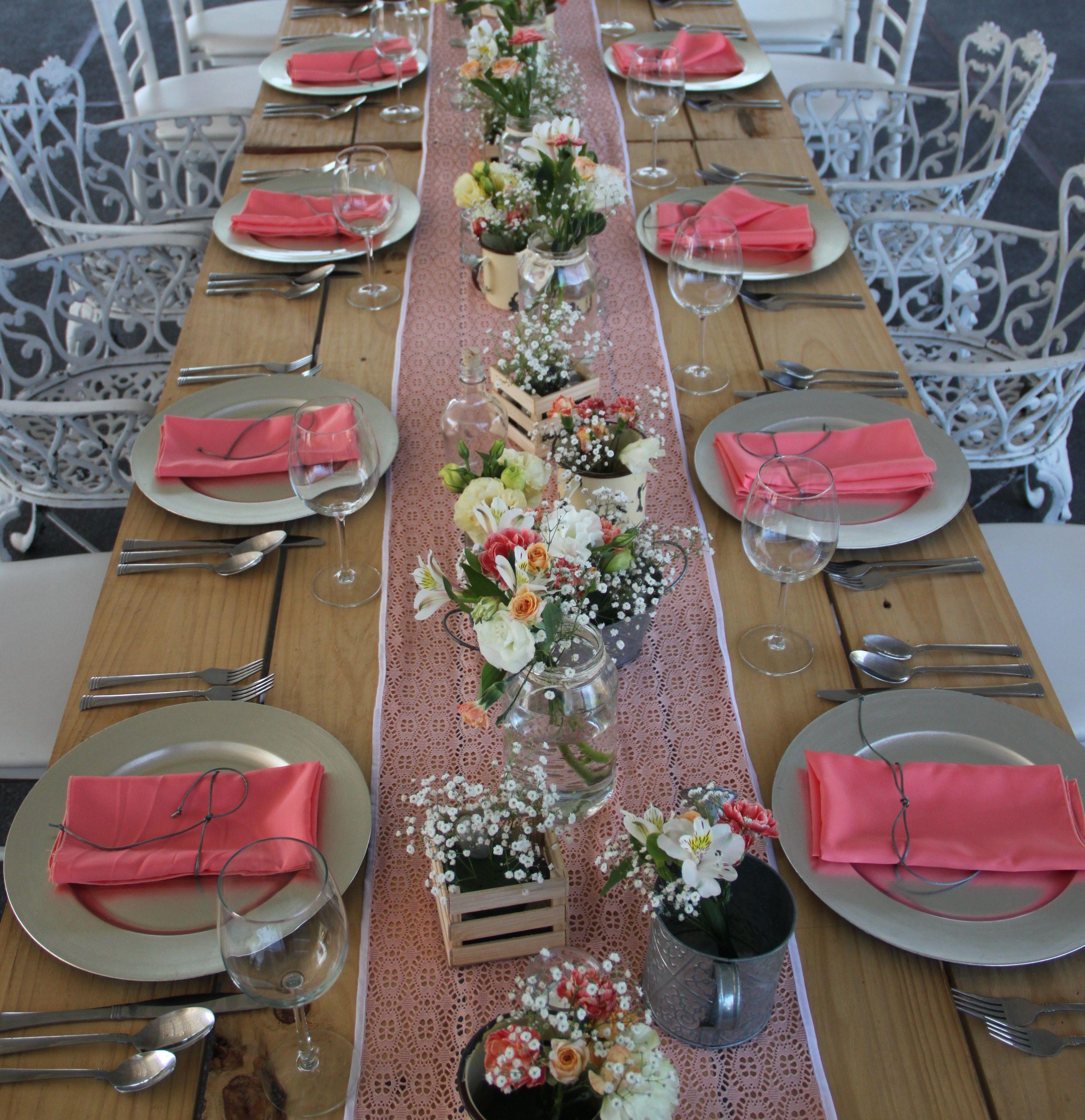 mesa de madera con un camino en color salmón que enmarca las flores ...