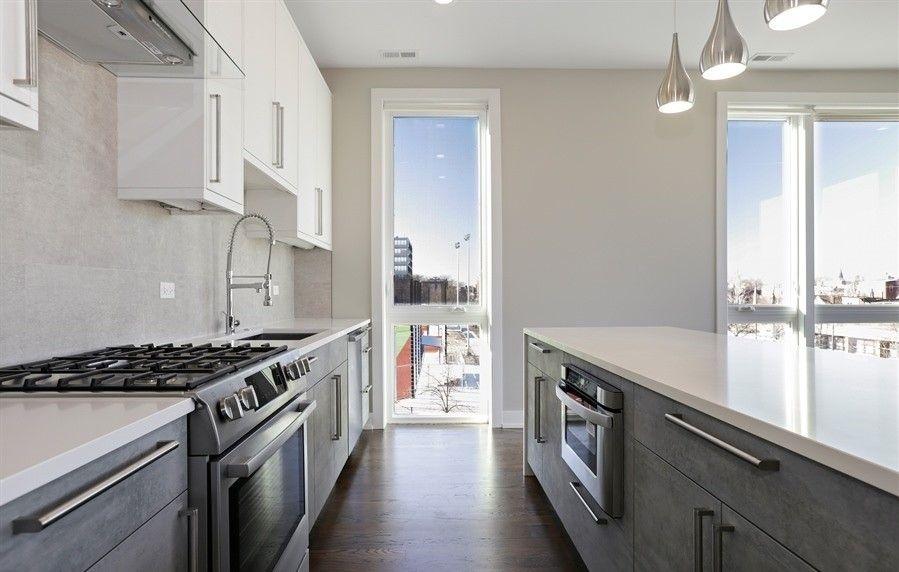 Modern White Kitchen With White Quartz Countertops Pendant