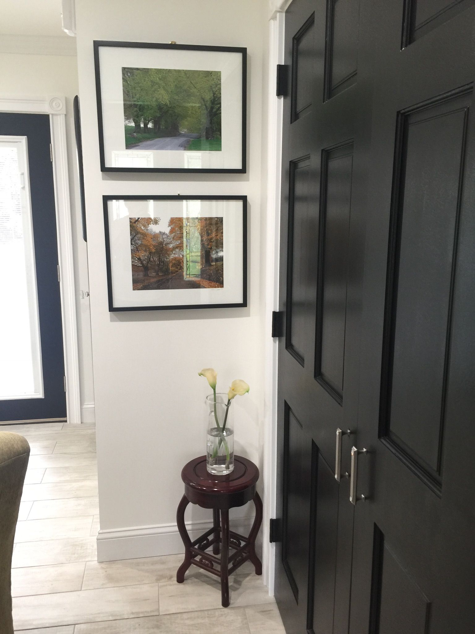 Linen closet with doors painted black and and nickel door handles