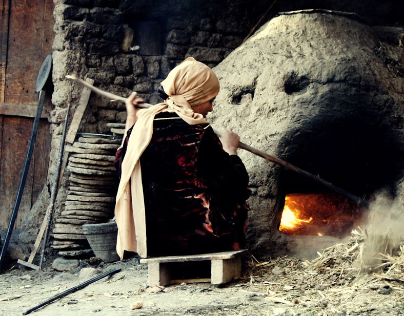 An Egyptian woman sits beside her oven and makes it ready for baking bread.