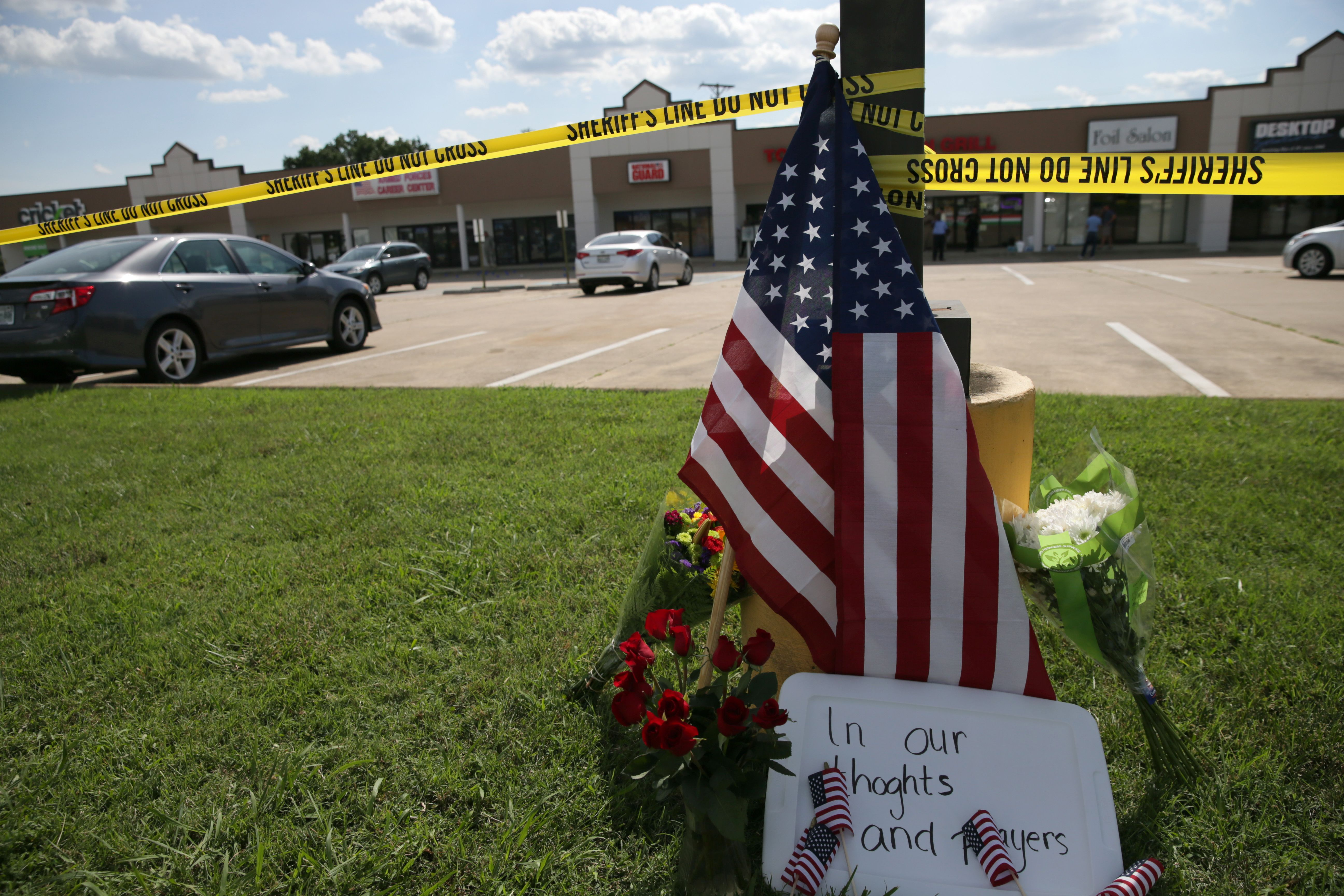 CHATTANOOGA, Tenn. (July 16, 2015) Police tape and a makeshift memorial frame the scene at an Armed Forces Career Center, where earlier in the day an active shooter opened fire, injuring one U.S. Marine. The gunman later moved to the nearby Navy Operational Support Center (NOSC) firing multiple shots, killing four Marines and injuring one Sailor. (U.S. Navy photo by Damon J. Moritz/Released)