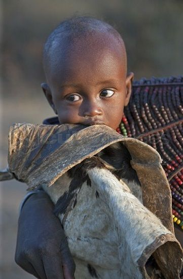 Africa | A Pokot child wrapped in a goatskin in his mother's arms. | Photographer Nigel Pavitt, © JohnWarburton-Lee/Cuboimages