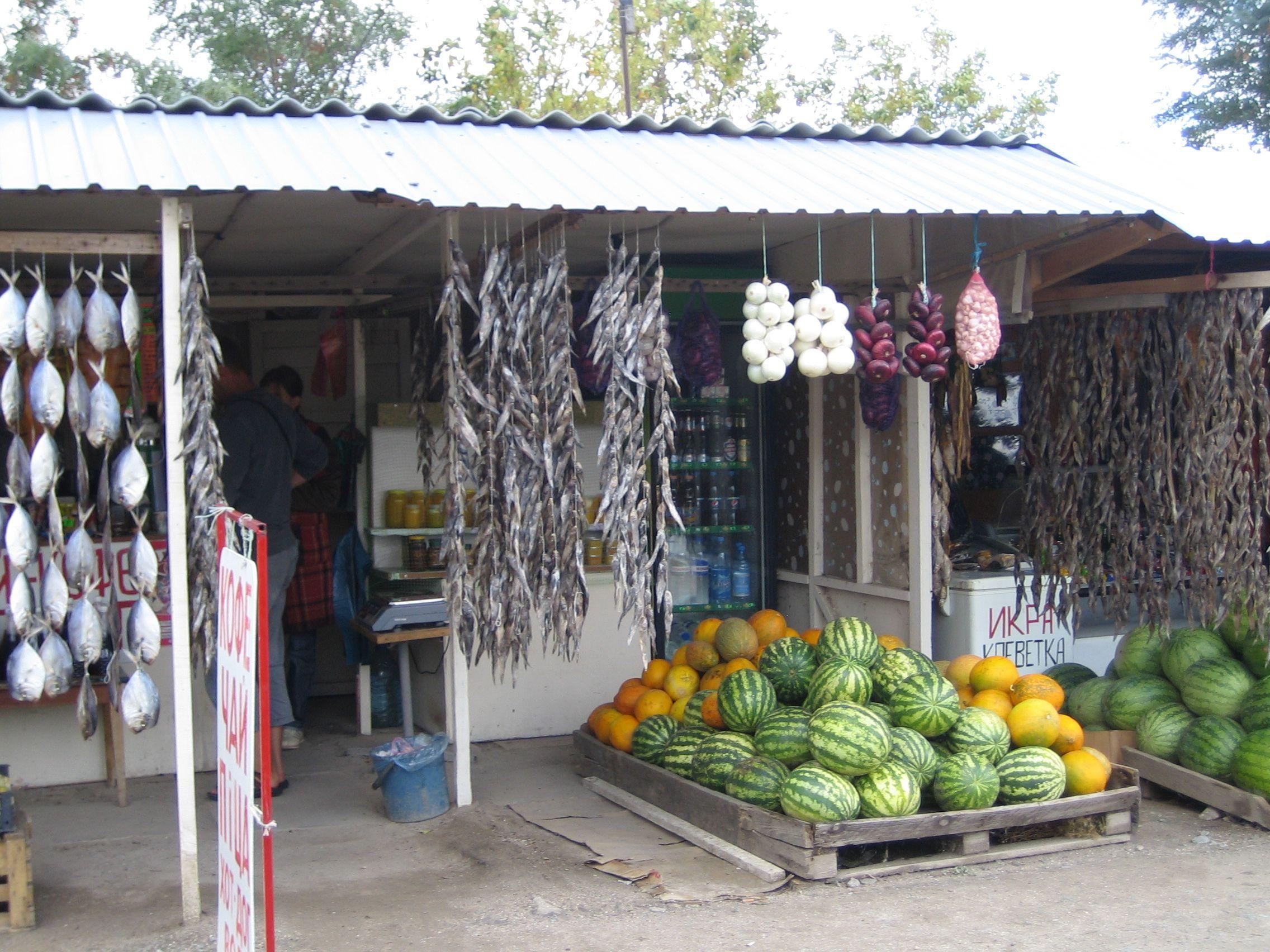 Un magasin : les poissons sèches au soleil à côté des fruits.