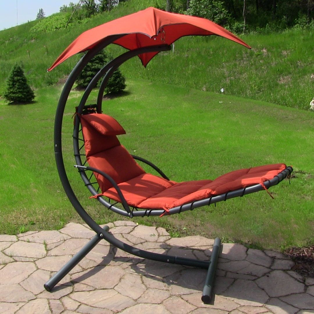 This outdoor hanging lounge chair features an umbrella to shade the