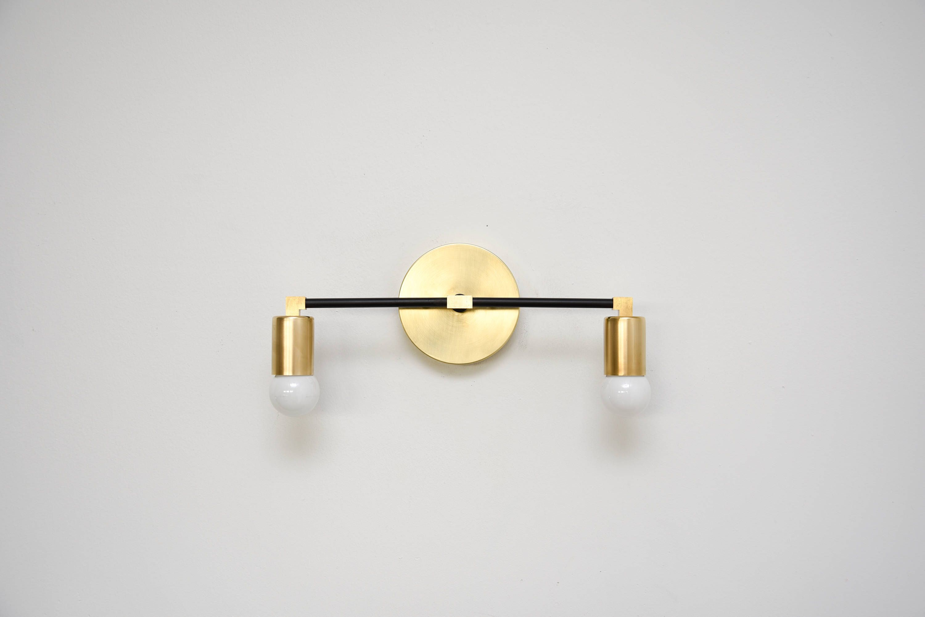 Stunning 2 bulb wall sconce available in brass black and brass mix