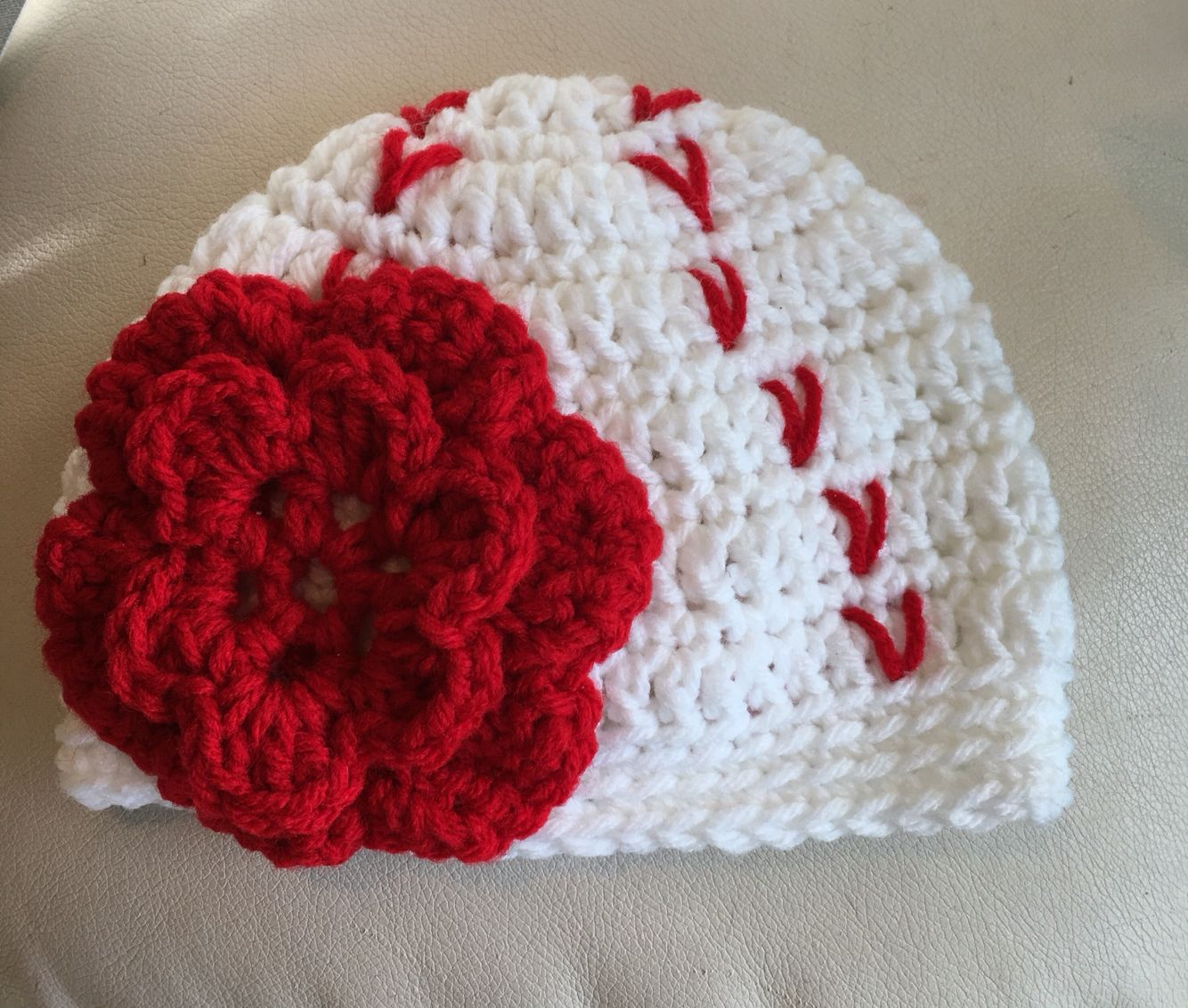Baseball hat for baby Englynd! Used this picture to look at stitching:   https://www.pinterest.com/pin/56365432810002978/ https://www.pinterest.com/pin/56365432811156468/ Used this as the base pattern and added a flower:  https://www.pinterest.com/pin/56365432807034936/