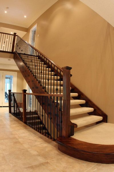 Traditional Staircase With Wooden And Metal Wrought Stair Railings
