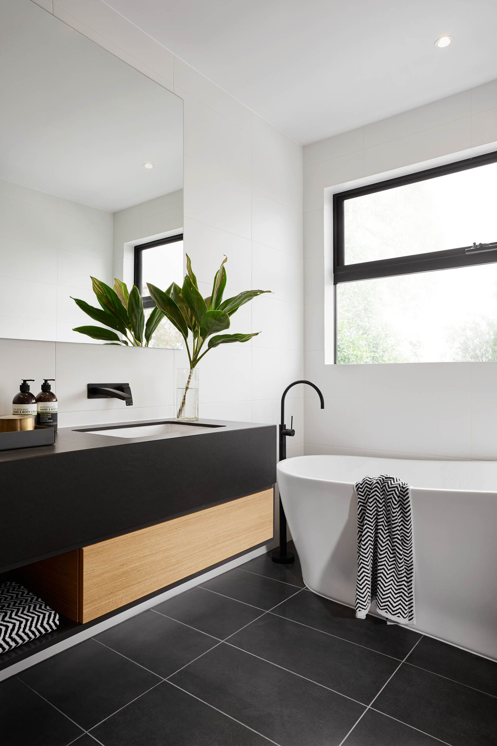 Modern black and white bathroom with black tile matte for Black tile bathroom designs