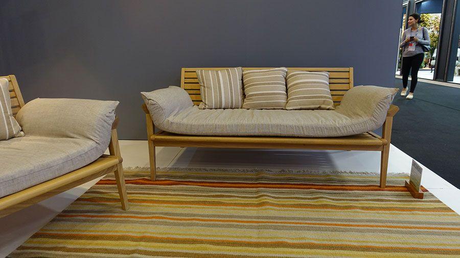 Parede cinza, tapete listrado, cadeira de madeira com estofado, lançamento da Butzke na Abimad 2017.