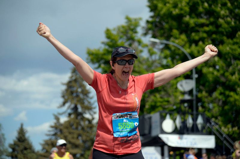 Description of . Jill Pitts raises her arms in joy after finishing the 1/2 marathon with a time of 3:35:24 in the 9th annual Colfax Marathon May 18, 2014. The 26.2 mile Marathon runs through Denver's iconic landmark Mile High Stadium (twice), Sloan's Lake, City Park, Colfax Avenue through Lakewood and Aurora. The Marathon started and finished in City Park where runners enjoyed the rest of the day listening to music by Chris Daniels and the Kings. (Photo by John Leyba/The Denver Post)